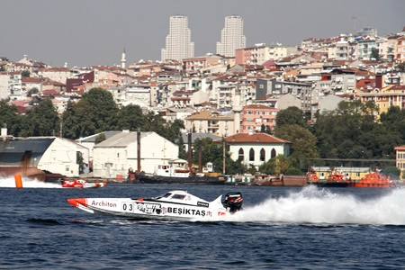 bateau de course: ISTANBUL - SEPTEMBER 25, 2010: An Off-Shore racing boat speeds along the water at the UIM World Offshore 225 Championship on the Golden-Horn bay. The pilots Ali TANIR and Murat LEKI drive for the BESIKTAS team