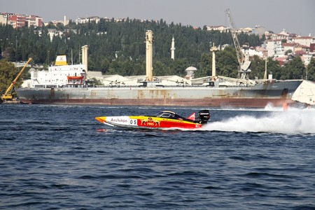 bateau de course: ISTANBUL - SEPTEMBER 25, 2010: An Off-Shore racing boat speeds along the water at the UIM World Offshore 225 Championship on the Golden-Horn bay. Berna and Josef MUHLBAUER drive for the GALATASARAY team. �ditoriale