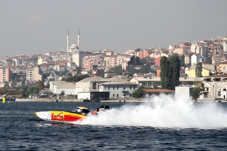 bateau de course: ISTANBUL - SEPTEMBER 25, 2010: An Off-Shore racing boat speeds along the water at the UIM World Offshore 225 Championship on the Golden-Horn. Berna and Josef MUHLBAUER drive for the GALATASARAY team �ditoriale