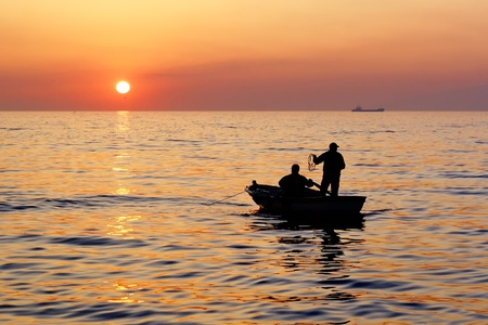 fishers: Fishermans boat in sunset Stock Photo