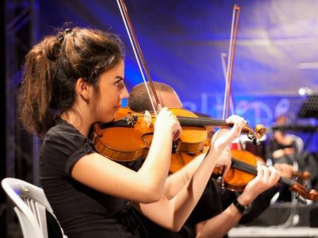 concerto: Estambul - 11 de julio: Los miembros de la Maltepe Orquesta Sinf�nica cantar en vivo en etapa de aire libre de Maltepe, 11 de julio de 2010 en Estambul, m�sico tocando viol�n Editorial