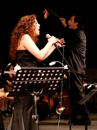 ISTANBUL - JULY 11: Members of the Maltepe Symphonic Orchestra perform live at Maltepe open air stage on July 11, 2010 in Istanbul. Soprano Selva Erdener with conductor Naci Ozguc