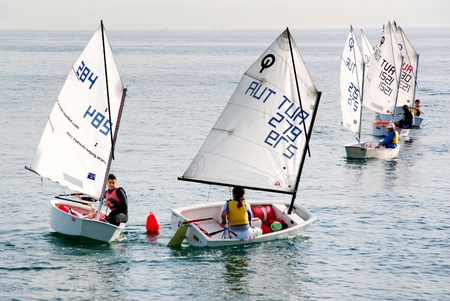 Istanbul, Turkey - November 2, 2008 : Girls train on optimist class yachts at Marmara sea. Sailors turn around red buoy