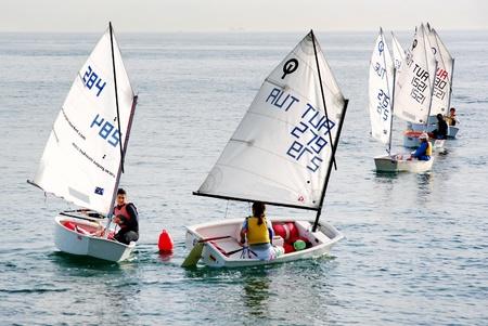 Istanbul, Turkey - November 2, 2008 : Girls train on optimist class yachts at Marmara sea. Sailors turn around red buoy