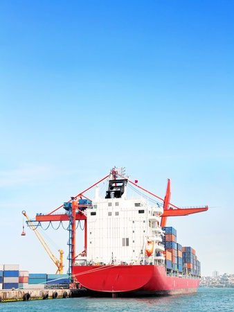 Red container ship under large blue sky