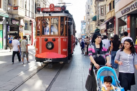 electric tram: ISTANBUL - JULY 06: Unidentified mother has 4 years old child enjoy themselves at Istiklal Street on July 06, 2010 in Istanbul. Istiklal St. is busiest shopping street and famous with nostalgic trams Editorial
