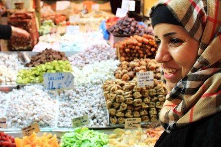 ISTANBUL - NOVEMBER 20: Unidentified woman bargains for Turkish Delight at Spice Market on November 20, 2010 in Istanbul. Nut, locum and souvenirs fill shops at here, one of the oldest bazaars in city