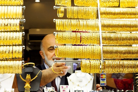 ISTANBUL - JUNE 9: Old sales man lines up bracelets on display at Grand Bazaar on June 9, 2011 in Istanbul. Turkish gold jewellery is a unique heritage which has been passed on from Romans and Ottomans