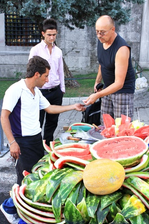 turkish people: ISTANBUL - AUGUST 31: People buy and eat fruits from street vendors during Lesser Bairam at Sultanahmet on August 31, 2010 in Istanbul, Turkey. In Ramadan Month temperature was over 35 degree in here Editorial