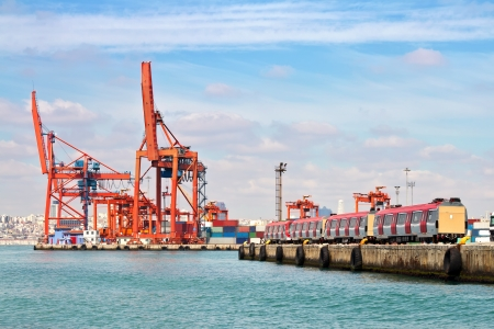Industrial harbor with large red cranes and a train photo