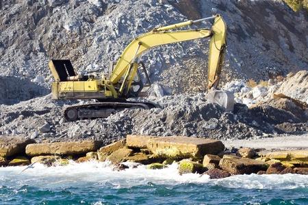 excavate: Excavator at construction site in a sea port