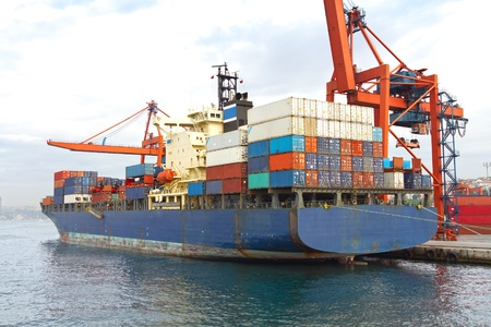 seaport: Blue cargo ship in port, fully loaded with containers