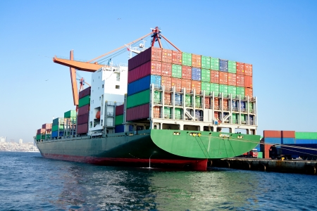 container port: Green cargo ship in port, fully loaded with containers Stock Photo