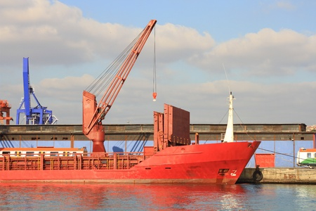Red freighter ship moored at the quayside photo