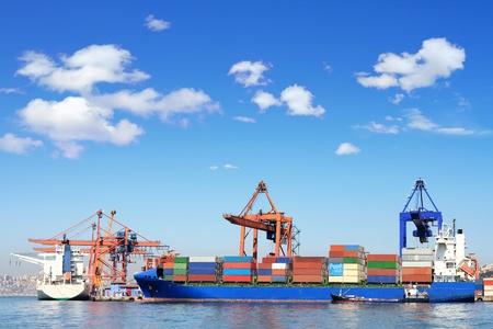 Cargo schip, containers en kranen in zeehaven Stockfoto