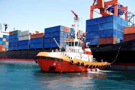 Sleepboot uit te trekken een containerschip Redactioneel
