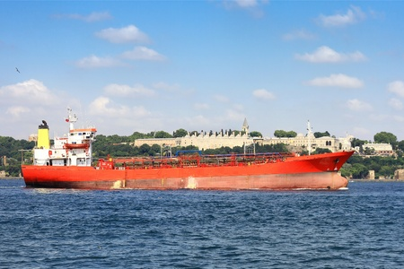 Red gas tanker sails in front of Topkapi Palace in Istanbul photo