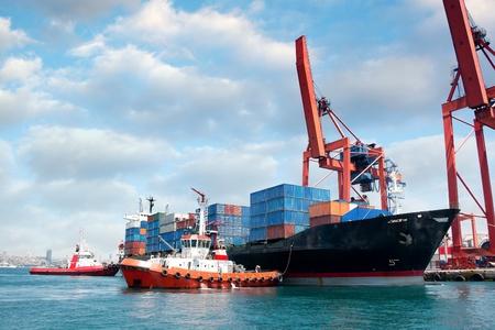 Rimorchiatori tirando fuori nave portacontainer
