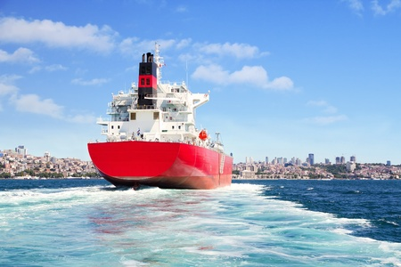nautical vessels: Red cargo ship sailing in to the sea
