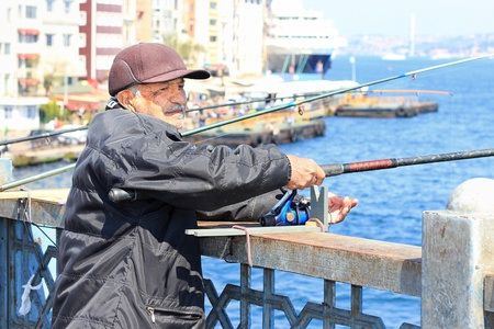 ISTANBUL - APRIL 12: An unidentified senior man fishing on Galata Bridge on April 12, 2012 in Istanbul. The bridge is well known for rod fishing in here. Stock Photo - 13574413