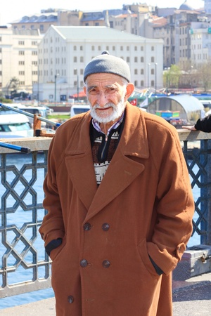 turkish man: ISTANBUL - APRIL 12: Portrait of an unidentified senior Turkish man wearing traditional dress on Galata Bridge on April 12, 2012 in Istanbul. The bridge is major strolling and tourism center in city.