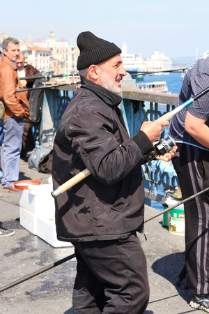 ISTANBUL - APRIL 12: An unidentified senior man fishing on Galata Bridge on April 12, 2012 in Istanbul. The bridge is well known for rod fishing in here.