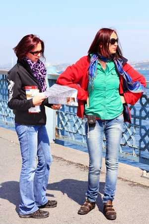 ISTANBUL - APRIL 12: Unidentified travellers holding a city map on Galata Bridge of Goldenhorn on April 12, 2012 in Istanbul. The bridge is the major strolling and tourism center in city.