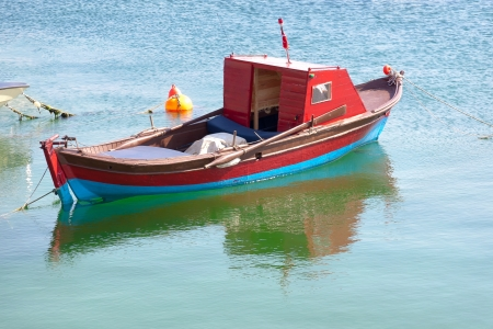 Wooden red row boat in calm water Stock Photo - 13670793