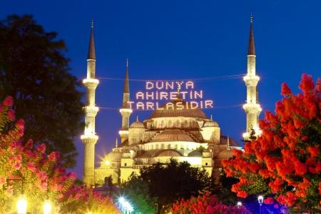 ISTANBUL - 25 juli: Moskee lichten straten van de stad te verlichten tijdens de maand Ramadan op 25 juli 2012 in Istanbul. Berichten die door licht gespannen tussen minaretten gespeld is een traditie in Turkije. Blauwe Moskee in de Ramadan maand, Istanbul, Turkije
