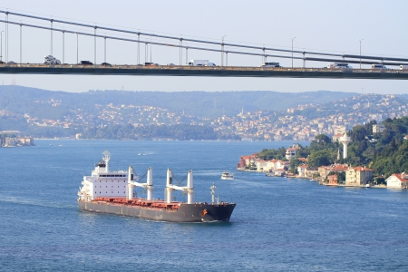 full suspended: Transportation with a cargo ship sailing under the bridge Stock Photo