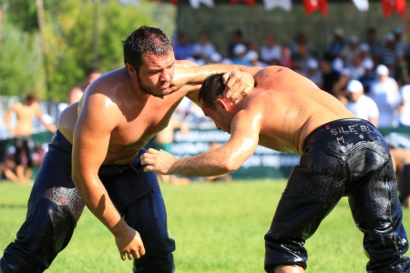 greased: ISTANBUL - AUGUST 24: Unidentified wrestlers in the 8th Sile Annual Oil Wrestling Event on August 24, 2012 in Istanbul. Wrestlers trying to hand-back of opponents neck Editorial