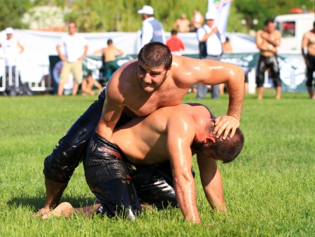 latter: ISTANBUL - AUGUST 24: Unidentified wrestlers in the Sile Annual Oil Wrestling Event on August 24, 2012 in Istanbul. Pehlivan aims to control his opponent by putting his arm through the latter Editorial