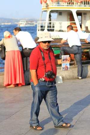 eminonu: ISTANBUL - AUGUST 27: Portrait of a street photographer at Eminonu Pier on August 27, 2012 in Istanbul. Eminonu is main tourism and trade zone in the city.