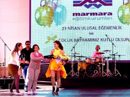 director de escuela: ESTAMBUL - 22 de abril: El cantante Atiye realiza para los ni�os durante la Soberan�a Nacional y el D�a del Ni�o el 22 de abril de 2012 en Estambul. Atiye La estrella del pop con el director en la ceremonia de concierto.