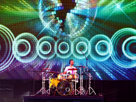 drum kit: ISTANBUL - APRIL 22: Singer Atiye performs for the children during National Sovereignty and Children Day on April 22, 2012 in Istanbul. Drummer plays in front of large LED screen.