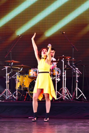 onstage: ISTANBUL - APRIL 22: Singer Atiye performs for the children during National Sovereignty and Children Day on April 22, 2012 in Istanbul. Singer holds her microphone to fans in the pit to sing along.
