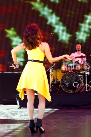 ISTANBUL - APRIL 22: Singer Atiye performs for the children during National Sovereignty and Children Day on April 22, 2012 in Istanbul. Beautiful girl in yellow dress sings a very catchy song
