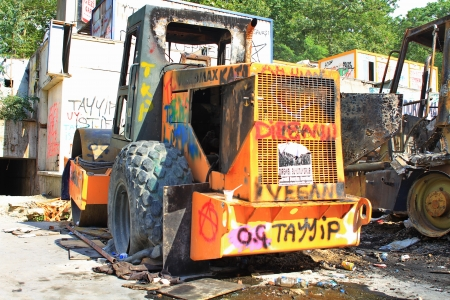 dissident: ISTANBUL - JUN 13: Peaceful protest over Gezi Park turns violent as police crack down on June 13, 2013 in Istanbul. A destroyed road roller is seen in worksite after clashes at Taskim square.