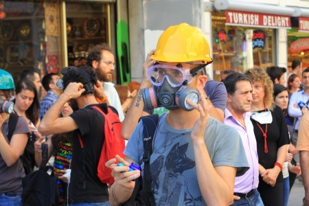 nationwide: ISTANBUL - JUN 17: Five labor unions call 1-day nationwide strike on Monday over crackdown on June 17, 2013 in Istanbul, Turkey. A demonstrator wearing gas-mask and glasses to protect from pepper gas at Istiklal Street Editorial