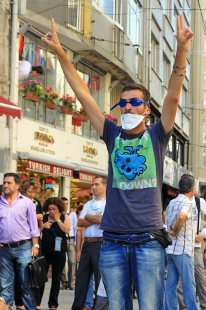 insurrection: ISTANBUL - JUN 17: Labor unions call 1-day nationwide strike over crackdown on June 17, 2013 in Istanbul, Turkey. A protester makes victory sign in front of riot police during the protest at Istiklal Street
