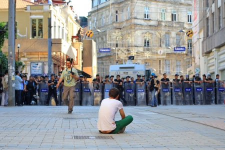 insurrection: ISTANBUL - JUN 17: Labor unions call 1-day nationwide strike over crackdown on June 17, 2013 in Istanbul, Turkey. A young man sits down in protest as demonstrating police brutality.