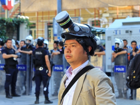 nationwide: ISTANBUL - JUN 17: Five labor unions call 1-day nationwide strike over crackdown on June 17, 2013 in Istanbul, Turkey. A journalist wearing gas-mask to protect from pepper gas at Istiklal Street