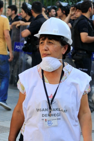 observers: ISTANBUL - JUN 17: Labor unions call 1-day nationwide strike over crackdown on June 17, 2013 in Istanbul, Turkey. Human rights members wearing white helmet and shirt, monitor possible abuses during demonstration Editorial