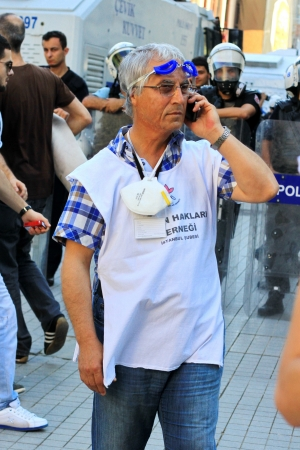 observers: ISTANBUL - JUN 17: Labor unions call 1-day nationwide strike over crackdown on June 17, 2013 in Istanbul, Turkey. Human rights member wearing white shirt, monitors possible abuses during the demonstration