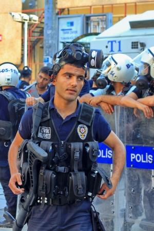 waits: ISTANBUL - JUN 17: Five labor unions call 1-day nationwide strike over crackdown on June 17, 2013 in Istanbul, Turkey. Police lined up on Istiklal Street during the protest. A policeman wearing full equipment belt waits on Istiklal Street Editorial