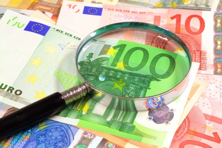 burning money: Euro paper notes  Perfect for any financial, commerce, treasury or banking needs  Magnifying glass over Euros Stock Photo