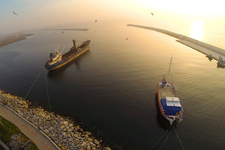 Fisher boat and a cargo ship berthed against sunset in calm sea. Aerial Shot. photo