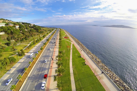 Car traffic on a typical dual carriageway. Aerial view of Sahilyolu Street at Kartal in Istanbul. Showing many cars and coastal street along Marmara Sea. Driving to nature on divided highway in a sunny day. Редакционное