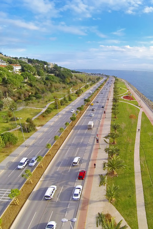 Driving to nature on divided highway in a sunny day. Aerial view of Sahilyolu Street at Kartal in Istanbul. Showing many cars and coastal street along Marmara Sea. Car traffic on a typical dual carriageway.