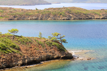 Datca Peninsula provides a natural boundary between the Gulf of Gokova in the Aegean Sea to the north, and the Gulf of Hisaronu in the Mediterranean Sea to the south. Along the 75 km from Marmaris to Datca, the road winds among trees and hills, opening on Фото со стока